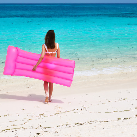 Woman with pink inflatable raft walking at the beach photo