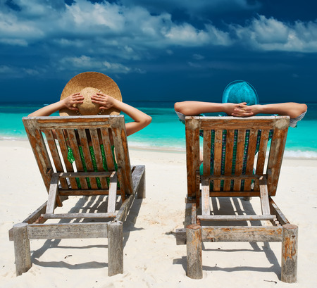 vacation destination: Couple in green on a tropical beach at Maldives