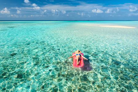 Frau entspannt auf Luftmatratze am Strand Lizenzfreie Bilder