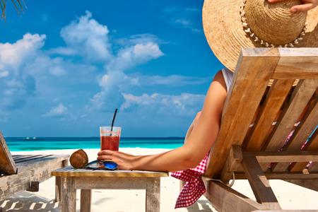 Frau am schönen Strand mit Chaise-Lounges
