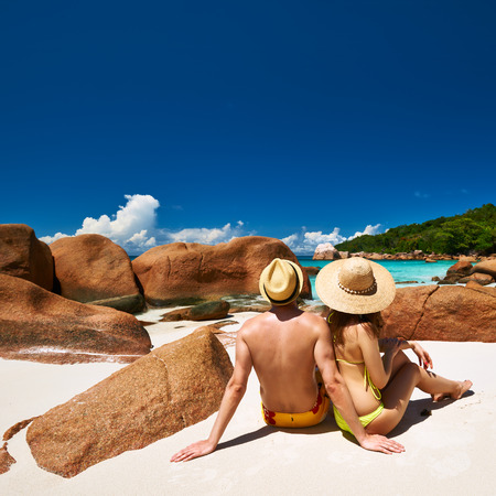 Couple sitting on a tropical beach at Seychelles photo