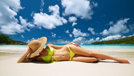 niñas en bikini: Mujer en bikini amarillo tirado en la playa tropical en las Seychelles Foto de archivo