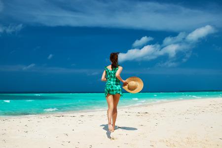 beach hat: Woman in green dress at tropical beach Stock Photo