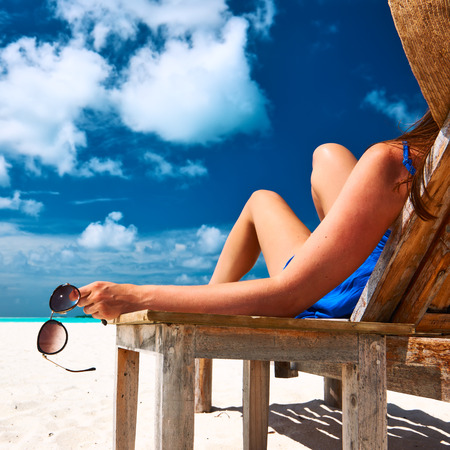Woman at beautiful beach holding sunglasses photo