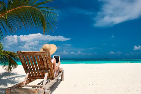 Junge Frau im Hut mit Tablet PC am Strand Standard-Bild - 37258755