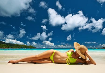 セーシェルで熱帯のビーチで横になっている黄色のビキニの女性