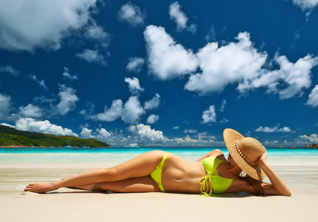 young bikini: Woman in yellow bikini lying on tropical beach at Seychelles