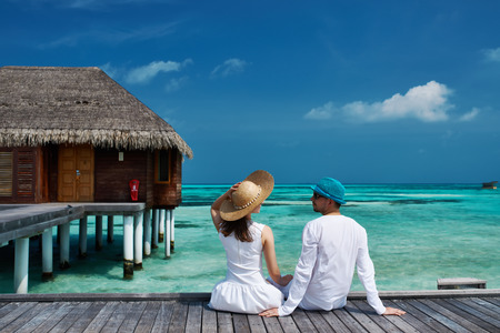 Couple on a tropical beach jetty at Maldives Imagens