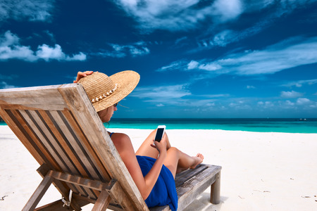 seaside resort: Young woman in hat with mobile phone at the beach Stock Photo