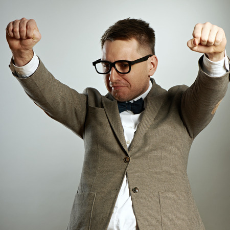 eccentric: Confident nerd in eyeglasses and bow tie enjoying success against grey background