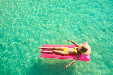 relaxation: Woman relaxing on inflatable mattress at the beach