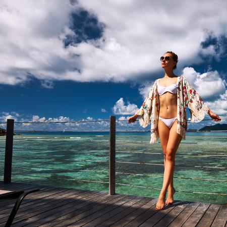 sarong: Woman with sarong on a tropical beach jetty at at Seychelles, La Digue.