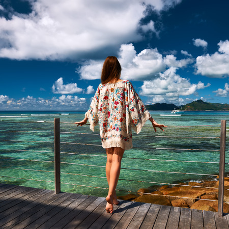 travel destinations: Woman with sarong on a tropical beach jetty at at Seychelles, La Digue.