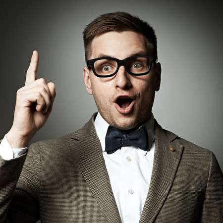 Confident nerd in eyeglasses and bow tie against grey background photo