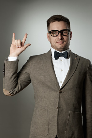Nerd in eyeglasses and bow tie showing rock on gesture against grey background photo