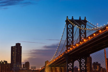 Manhattan Bridge and skyline silhouette view from Brooklyn in New York City at sunset photo