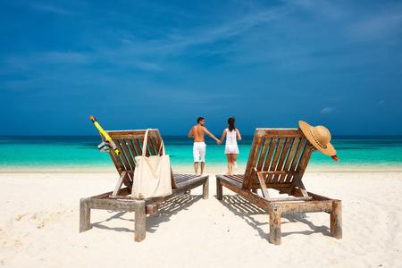 luna de miel: Pareja en marcha blanca en una playa tropical en las Maldivas