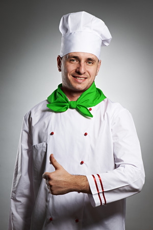 Male chef with thumb up portrait against grey background photo