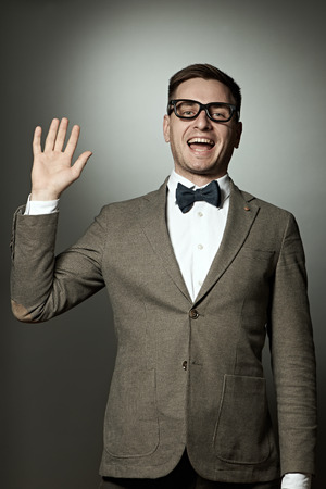 Nerd in eyeglasses and bow tie says Hello against grey background photo