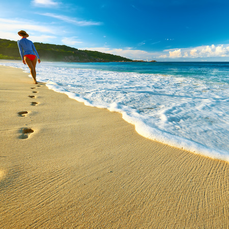 Woman at beautiful beach at Seychelles walking on sand. Focus on footprints. photo