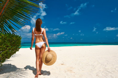 Woman in bikini on a tropical beach at Maldives photo