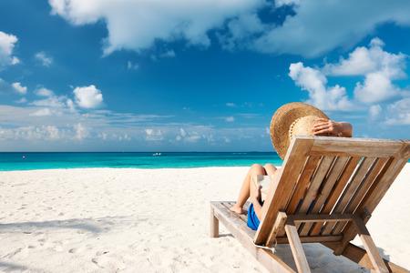 Mladá žena čtení knihy na pláži Reklamní fotografie