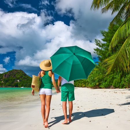 Couple in green with umbrella on a tropical beach at Seychelles photo