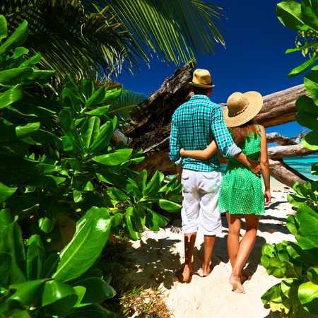 Couple walking to the beach Anse Source dArgent among tropical foliage at Seychelles, La Digue. photo