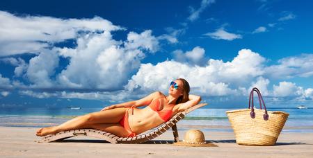 bikini island: Woman in bikini lying on tropical beach at Seychelles Stock Photo