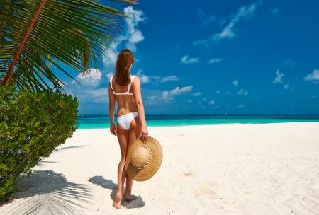 Woman in bikini on a tropical beach at Maldives photo