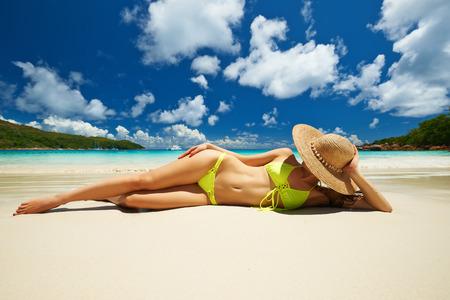 yellow bikini: Donna in bikini giallo sdraiato sulla spiaggia tropicale a Seychelles