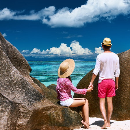 Couple relaxing among granite rocks on a tropical beach Anse Source dArgent at Seychelles, La Digue. photo