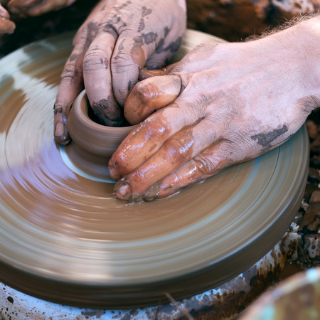 Hands working with clay on pottery wheel photo