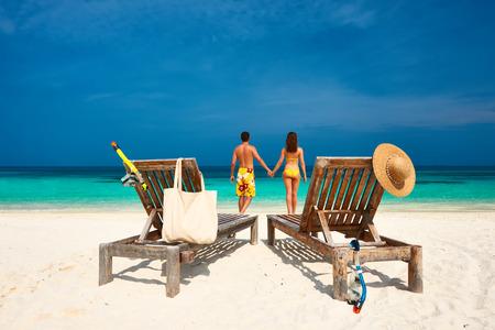 beach man: Couple in yellow on a tropical beach at Maldives