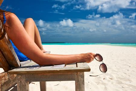 サングラスを保持している美しいビーチでの女性 写真素材