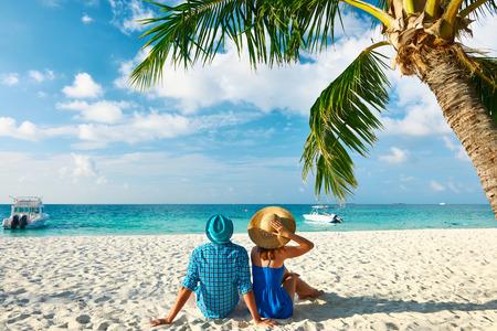 Pareja en ropa azul en una playa tropical en Maldivas