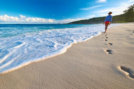 feet in sand: Woman at beautiful beach at Seychelles walking on sand. Focus on footprints.