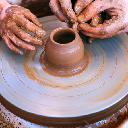 sculptor: Potters hands guiding childs hands to help him to work with the pottery wheel