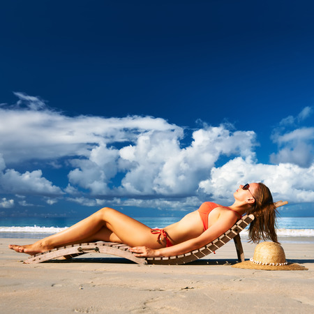 lounger: Woman in bikini lying on tropical beach at Seychelles Stock Photo