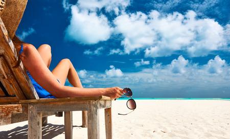 Žena na krásné pláži drží sluneční brýle