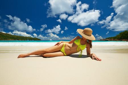 blue bikini: Woman in yellow bikini lying on tropical beach at Seychelles