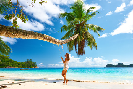 human palm: Woman in blue dress swinging at tropical beach Stock Photo