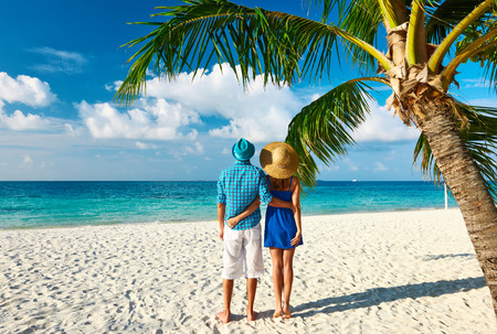 human palm: Couple in blue clothes on a tropical beach at Maldives