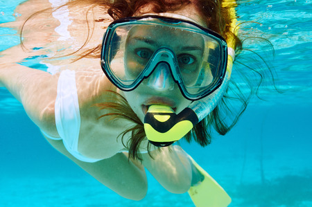 under water: Woman with mask snorkeling in clear water Stock Photo