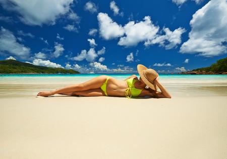 yellow bikini: Woman in yellow bikini lying on tropical beach at Seychelles