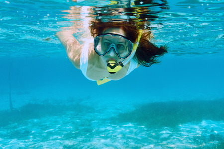 snorkeling: Woman with mask snorkeling in clear water Stock Photo