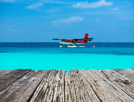 hydroplane: Twin otter red seaplane and old wooden pier at Maldives