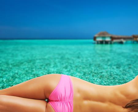 seins nus: Femme aux seins nus sur la belle plage avec bungalows sur pilotis à Maldives. Collage.