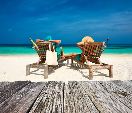 chair: Couple in green relax on a tropical beach at Maldives Stock Photo