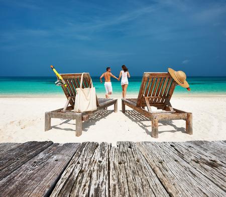 voyage: Couple en blanc se détendre sur une plage tropicale à Maldives Banque d'images